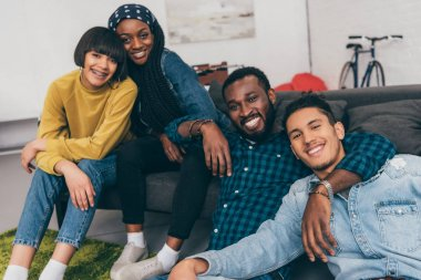 smiling multicultural young friends looking at camera