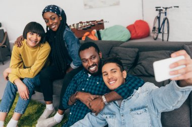 group of young multicultural smiling friends taking selfie on couch