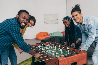 smiling group of multicultural friends playing table football
