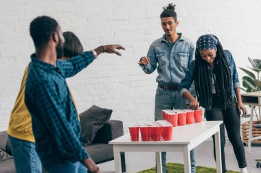 multiethnic group of friends playing beer pong at table