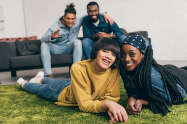 young smiling multiethnic women laying on rug and two male friends sitting behind