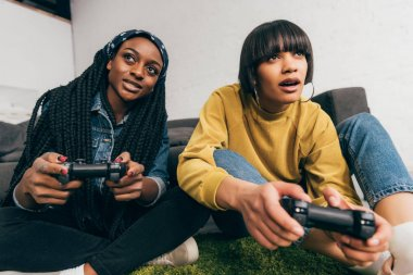 young multiethnic female friends sitting with joysticks playing video game