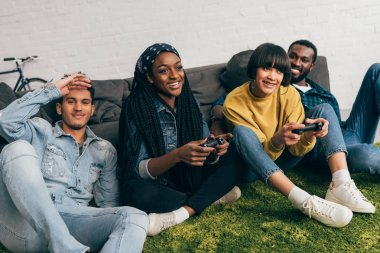 two young women playing video game by joysticks and male friends sitting beside