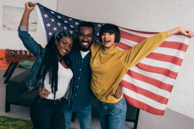 smiling young multiethnic friends standing with flag of USA