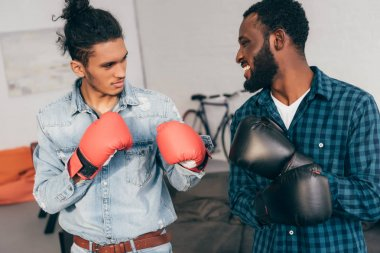 young multicultural male friends boxing in gloves