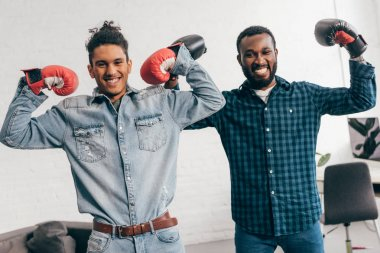 two smiling young men in boxing gloves standing with arms raised