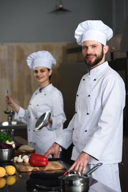 Professional chefs man and woman cooking in restaurant kitchen