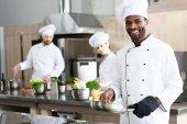 Afro-amerikai szakács főzés a többnemzetiségű kollégái