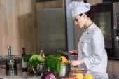 Profesionální žena kuchař řezání přísady na kuchyňském stole
