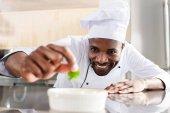 African american chef garnishing dish on restaurant kitchen