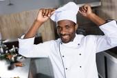 Fotografia Cuoco unico dellafroamericano mette toque bianco sulla testa