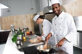 Multiracial male and female chefs team cooking by kitchen counter