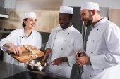 Multikulti-Köche bereiten in Restaurantküche Pilze zu