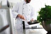 Oříznout obrázek šéfkuchař smažených potravin na pánev v restauraci kitchen