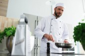 low angle view of handsome chef frying vegetables on frying pan at restaurant kitchen