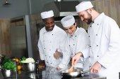 Multikulti-Köche braten in Restaurantküche Gemüse auf Pfanne