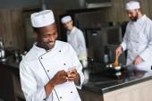 s úsměvem africké americké šéfkuchař pomocí smartphone v restauraci kitchen