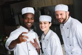 multicultural chefs taking selfie with smartphone at restaurant kitchen