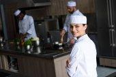 lächelnd schöne Köchin blickt in die Kamera in Restaurant-Küche