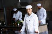 Lächelnder attraktiver Koch blickt in Restaurantküche in die Kamera