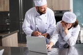 Köche nutzen Laptop in Restaurantküche und suchen Rezept