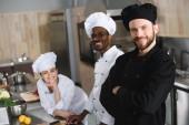 Lächelnde multikulturelle Köche blicken in Restaurantküche in die Kamera