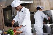 Afrikanisch-amerikanischer Koch schneidet Paprika in Restaurantküche