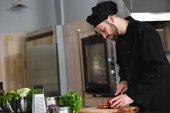 Seitenansicht des gutaussehenden Chefs, der Paprika in der Restaurantküche schneidet