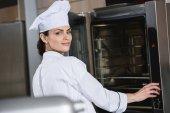 attraktiver Koch steht am Ofen in der Restaurantküche