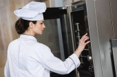 attractive chef setting oven for cooking at restaurant kitchen