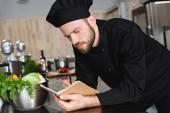 Seitenansicht des gutaussehenden Kochs, der in der Restaurantküche neue Rezepte auf Notizbuch schreibt