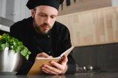 gutaussehender Koch schreibt in Restaurantküche neues Rezept ins Notizbuch