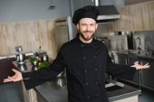 smiling handsome chef standing with open arms at restaurant kitchen