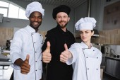 Lächelnde multikulturelle Köche zeigen Daumen hoch in Restaurantküche