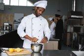 Afrikanisch-amerikanischer Koch presst Zitronen in Restaurantküche