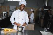 lächelnd gut aussehender afrikanisch-amerikanischer Koch, der in der Restaurantküche Zitronen auspresst