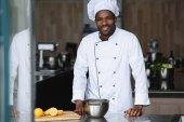 schöner afrikanisch-amerikanischer Koch steht in der Restaurantküche in der Nähe der Küchentheke