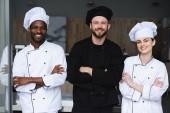 Lächelnde multikulturelle Köche stehen mit verschränkten Armen in der Restaurantküche und blicken in die Kamera