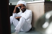 exhausted african american chef sitting on floor at restaurant kitchen and looking away