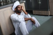tired african american chef sitting on floor at restaurant kitchen and looking away