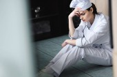 sad chef sitting on floor at restaurant kitchen