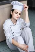 attractive chef sitting on floor at restaurant kitchen