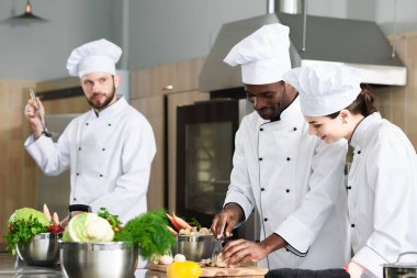 Multiracial chefs team sharing experience while cooking on modern kitchen