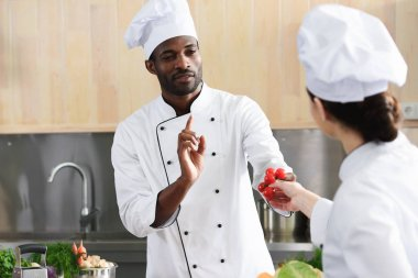 African american chef and female cook sharing cooking ingredients on kitchen