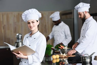 Female chef checking recipe in book by her multiracial colleagues