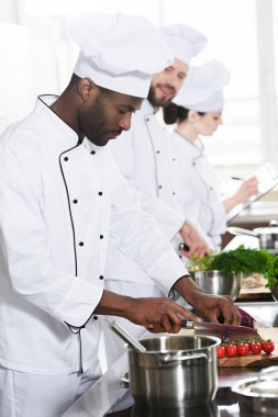 Multiracial chefs team cutting ingredients by kitchen table