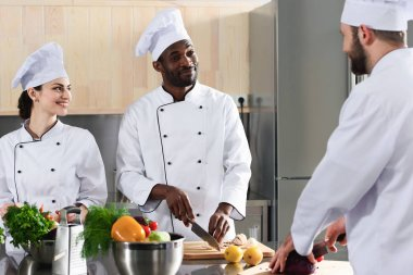Multiracial team of cooks cutting vegetables on kitchen table