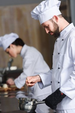 Male cook working by his female colleague on modern kitchen