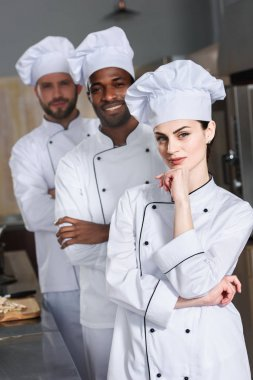 Multiracial team of cooks wearing white uniform in restaurant kitchen