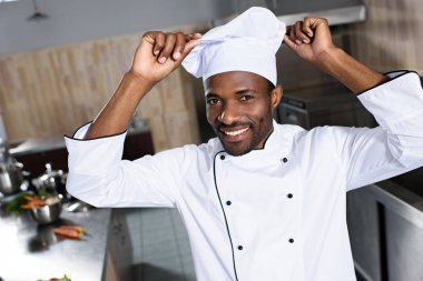 African american chef putting white toque on his head